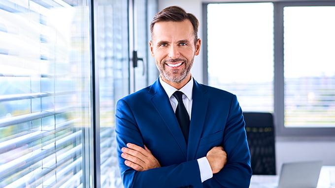 Un homme d'affaires en costume bleu à côté de la fenêtre de son bureau de travail.