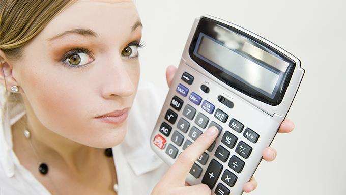 Femme avec une calculatrice à la main pour calculer un salaire