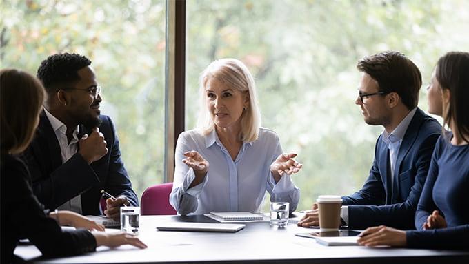 Réunion de travail, une femme au cheveux mi-longs, blancs, avec deux personnes à sa droite et deux personnes à sa gauche