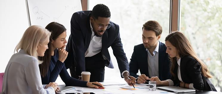 Une équipe de 5 personnes autour d'une table regarde des documents.