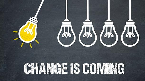 """Un dessin en craie sur un tableau en ardoise : un titre """"Change is coming"""" et 5 ampoules dont une allumée en jaune."""